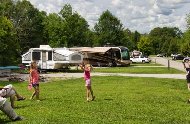 Family playing in open campsite setting