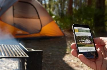 hand holding an iphone making camping reservation
