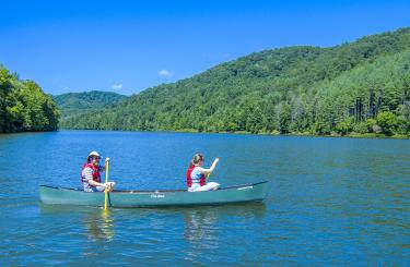 Couple on a blue sky day paddling a canoe on the lake with mountains in background